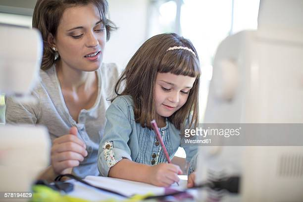 Mother and daughter designing clothes at home