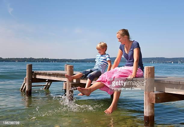 mère et fille de tremper les pieds dans le lac - starnberg photos et images de collection