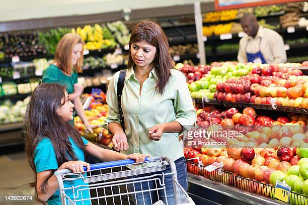 Mother and daughter discussing grocery purchases at the supermarket