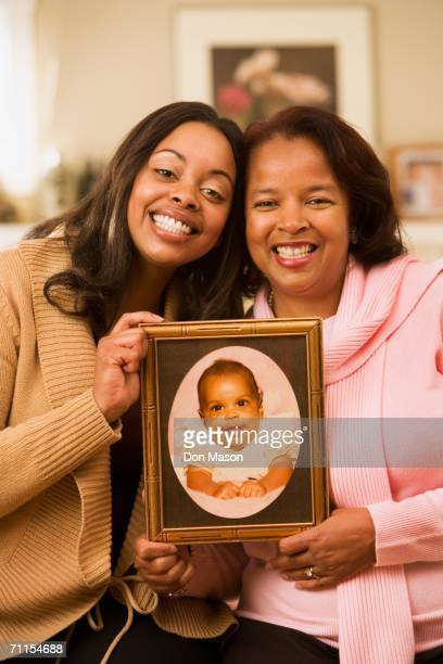Mother and daughter displaying a baby picture