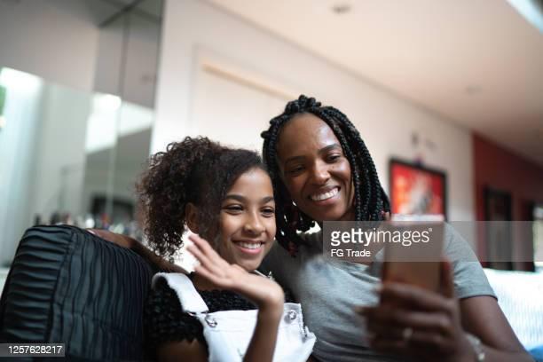 mutter und tochter machen einen videoanruf zu hause - mother daughter webcam stock-fotos und bilder