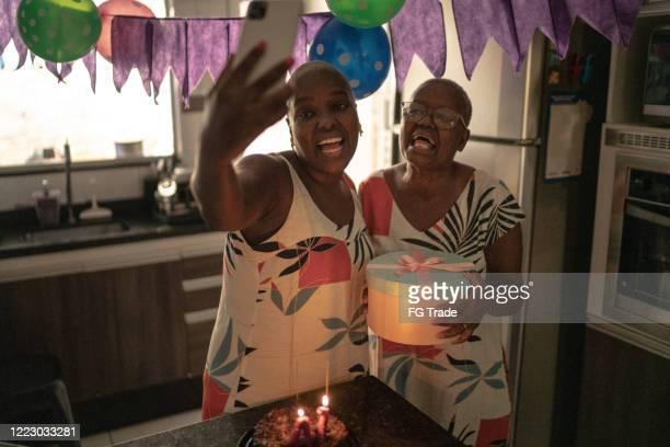 mutter und tochter machen einen videoanruf auf dem handy feiern geburtstags-distanz-party - misses vlog stock-fotos und bilder