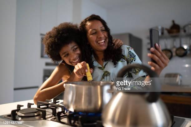 mutter und tochter machen einen videoanruf beim gemeinsamen kochen zu hause - mother daughter webcam stock-fotos und bilder