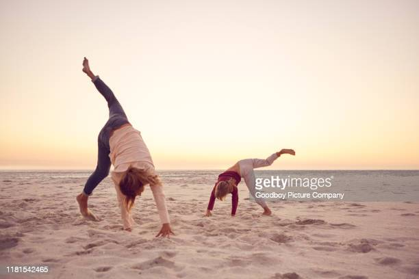 mother and daughter doing cartwheels together at the beach - cartwheel stock pictures, royalty-free photos & images