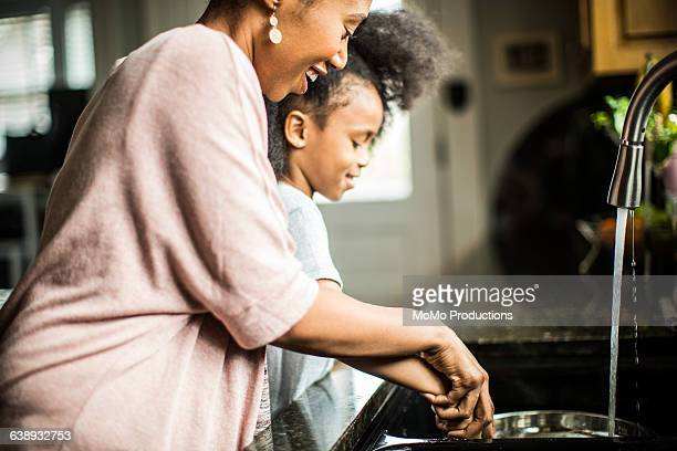 mother and daughter doing dishes