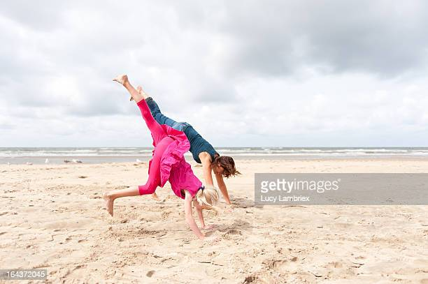 mother and daughter doing handstand on the beach - girl in dress doing handstand stockfoto's en -beelden