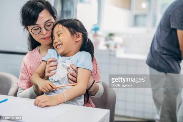 matriz e filha que fazem trabalhos de casa e que têm o divertimento - fazendo cócegas - fotografias e filmes do acervo