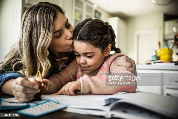 mother and daughter (7 yrs) doing homework - kissing stock pictures, royalty-free photos & images