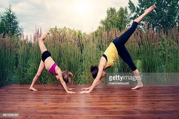Madre e hija haciendo yoga en verano naturaleza.