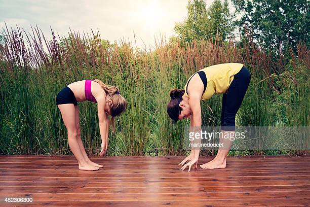 Mother and daughter doing yoga in summer nature.