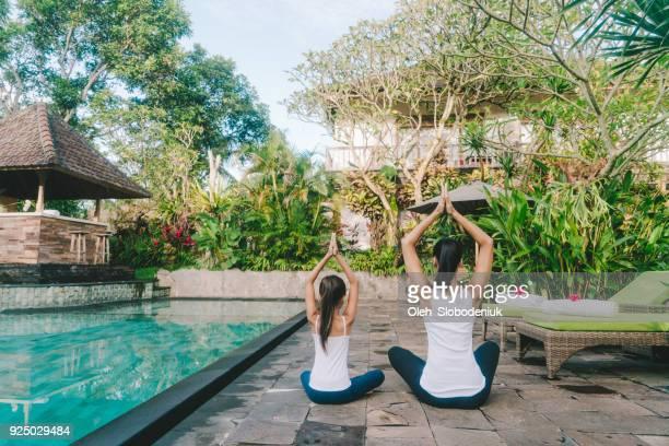 mère et fille faire la position du lotus yoga près de piscine - bonne posture photos et images de collection