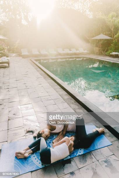 Mother and daughter  doing yoga near  swimming pool