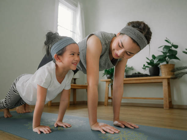 mother and daughter doing yoga - parents and children at home stock pictures, royalty-free photos & images
