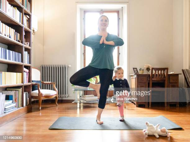 mother and daughter doing yoga together - lockdown stock pictures, royalty-free photos & images
