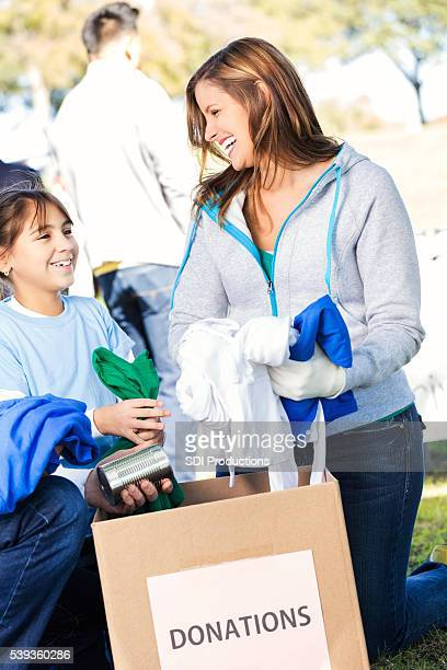 Mother and daughter donate clothing at charity event