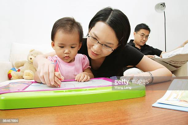 Mother and daughter drawing, father sitting and reading newspaper