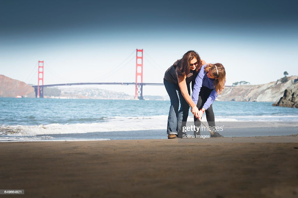 Mother and daughter drawing in sand on beach, San Francisco, California, United States : Stock Photo