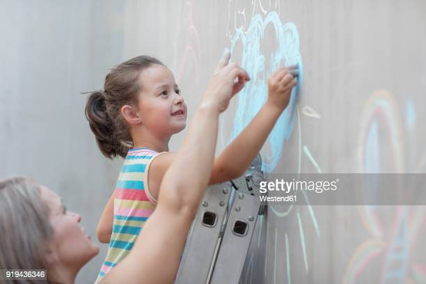 mother and daughter drawing with chalk on a concrete wall - chalk wall stock pictures, royalty-free photos & images