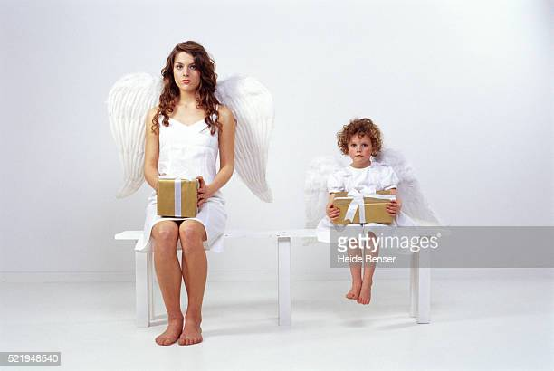 Mother and daughter dressed as angel, holding present