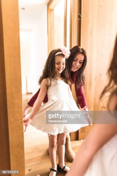 mother and daughter dressing up at the mirror