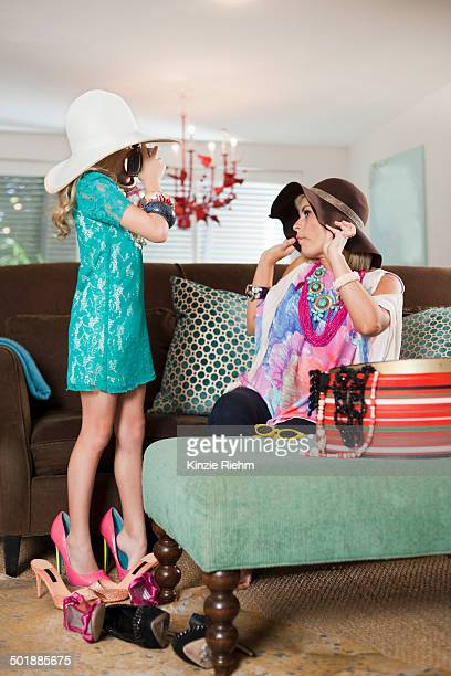 mother and daughter dressing up in hats and high heels - tacchi alti foto e immagini stock