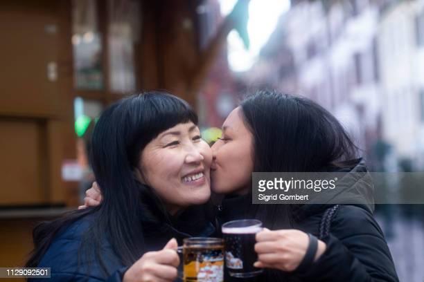 mother and daughter drinking at christmas market, freiburg, baden-wurttemberg, germany - sigrid gombert stock-fotos und bilder