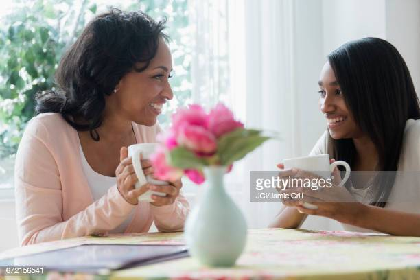 Mother and daughter drinking coffee in restaurant