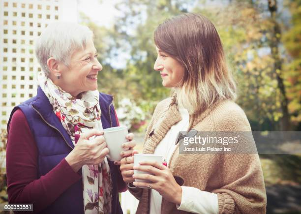 Mother and daughter drinking coffee outdoors