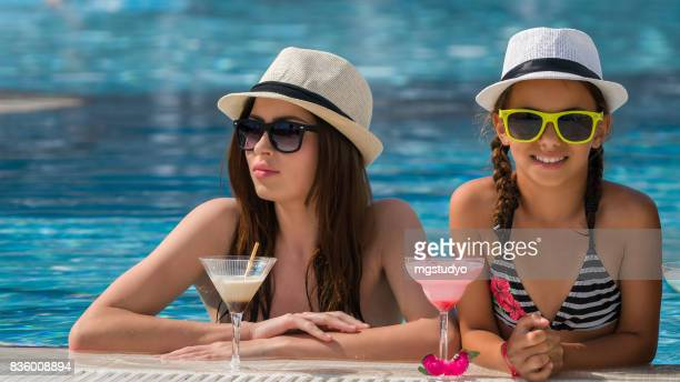 Mother and daughter drinking coktail  in swimming pool