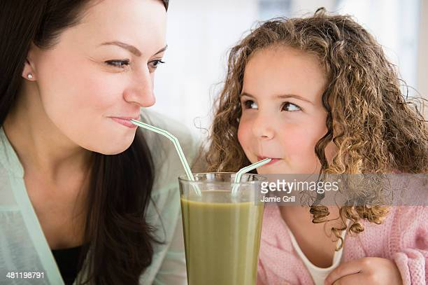Mother and daughter drinking green smoothie