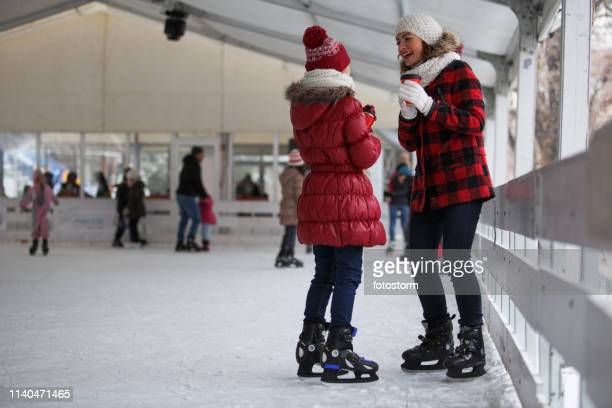 アイスリンクでお茶を飲む母と娘 - スケート靴 ストックフォトと画像