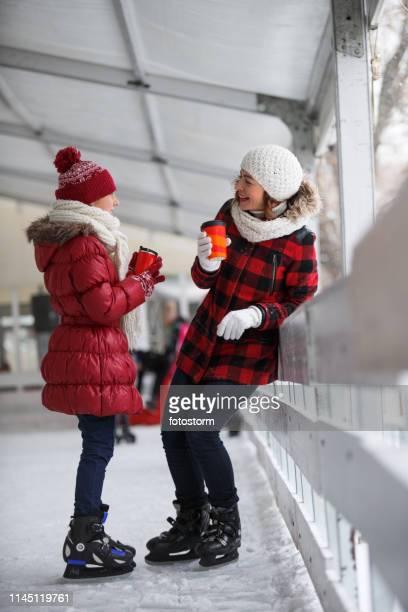 madre e hija bebiendo té en la pista de hielo - enero fotografías e imágenes de stock