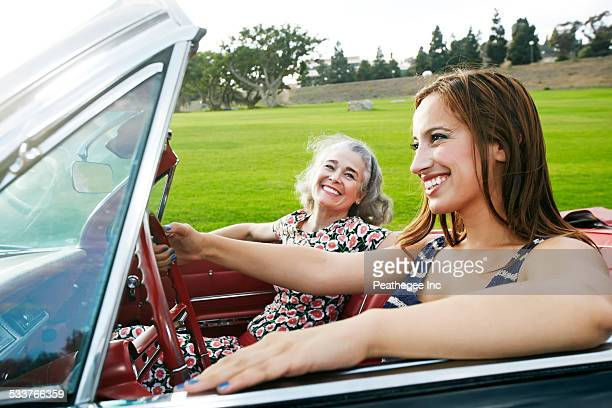 Mother and daughter driving in classic convertible