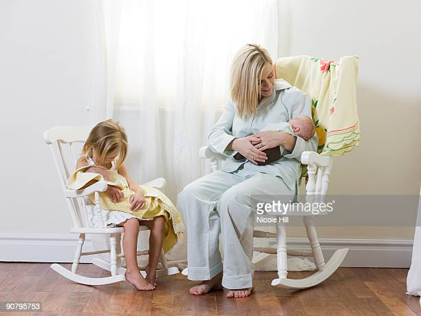 mother and daughter each holding a newborn baby
