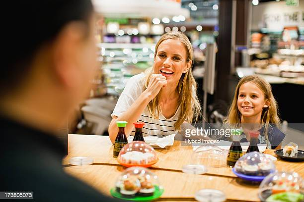 Mother and daughter eating at deli