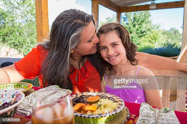 mother and daughter eating at table - indian girl kissing stock photos and pictures