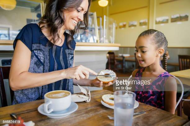 mother and daughter eating breakfast in cafe - spreading stock pictures, royalty-free photos & images