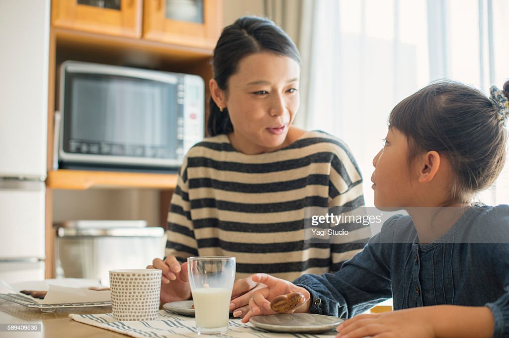 Mother and daughter eating cookies : Stock Photo