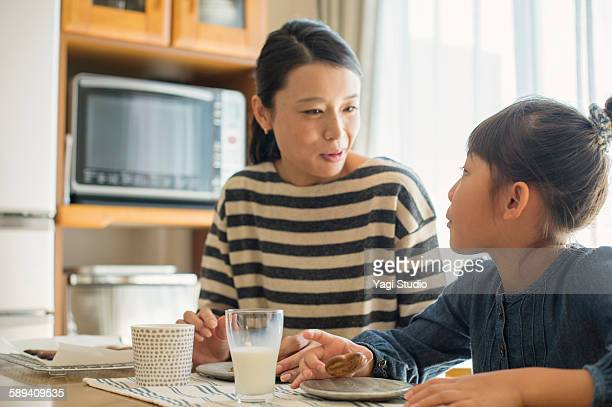 Mother and daughter eating cookies