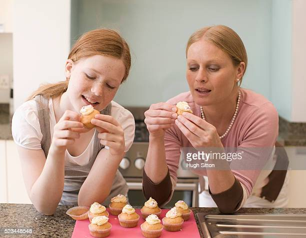 mother and daughter eating cupcakes - hugh sitton stock pictures, royalty-free photos & images