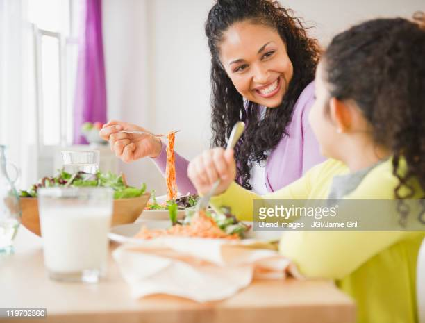Mother and daughter eating dinner together