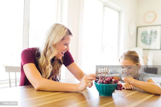 Mother and daughter (6-7) eating grapes