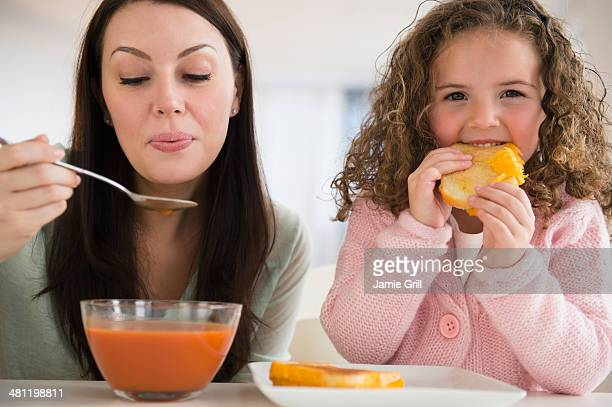 Mother and daughter eating grilled cheese and soup