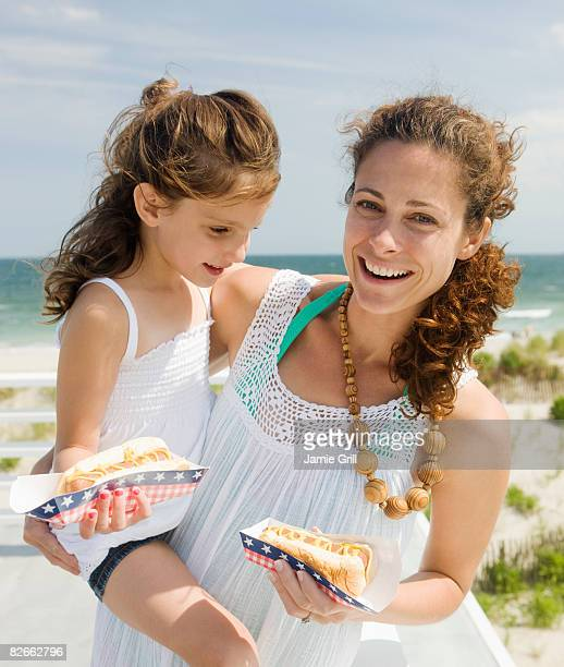 Mother and Daughter Eating Hot Dogs at Beach