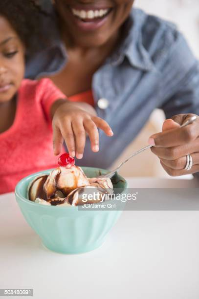 Mother and daughter eating ice cream sundae