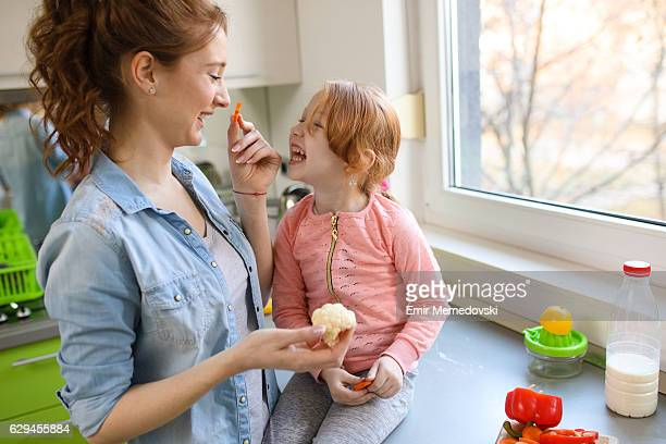 Mother and daughter eating vegetable in the kitchen.