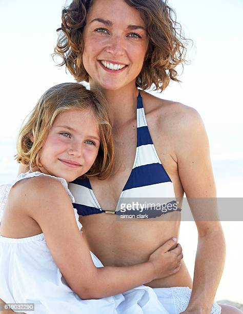 mother and daughter embrace on beach