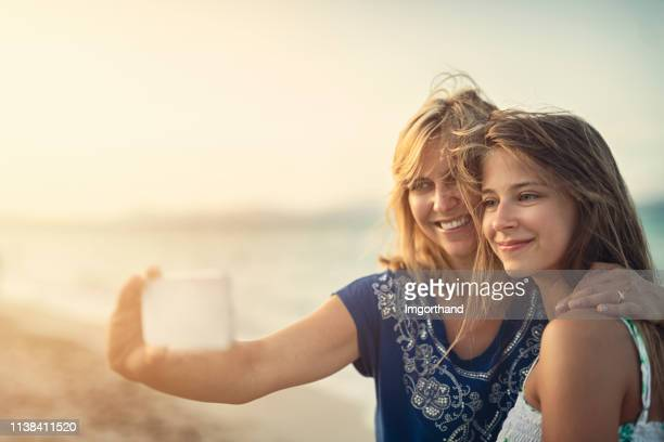 mother and daughter embracing and taking selfies at the beach - daughter stock pictures, royalty-free photos & images