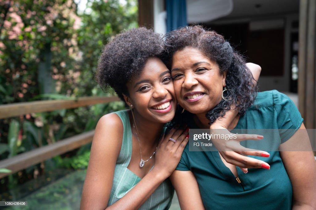 Mãe e filha, abraçando-se em casa : Foto de stock