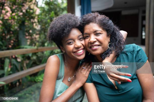 mother and daughter embracing at home - black stock pictures, royalty-free photos & images